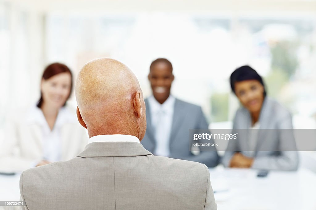 Senior man being interviewed by blur business people : Stock Photo