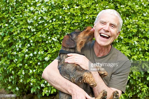 Senior man being licked by pet dog