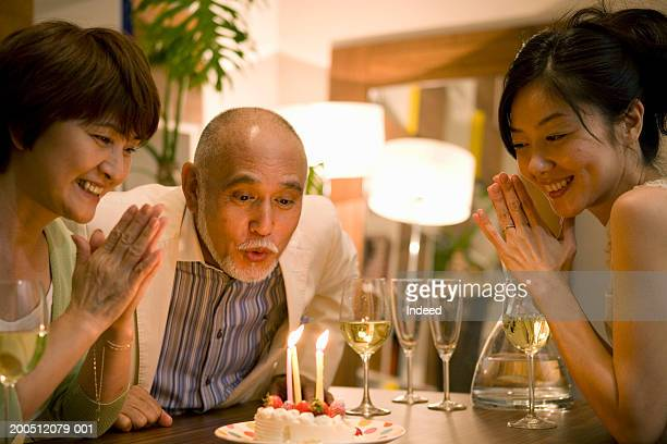 Senior man blowing out candles on birthday cake at dinner table