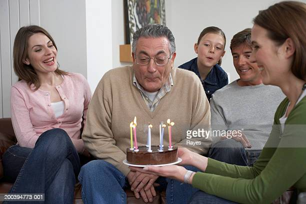 Senior man blowing out candles on cake, surrounded by family, smiling