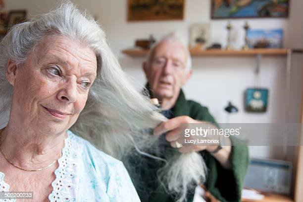 Senior man brushing his wife's long grey hair
