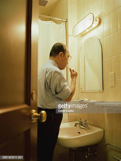Senior man brushing teeth in bathroom, side view