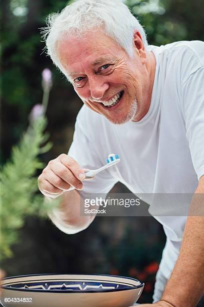Senior Man Brushing Teeth Outdoors