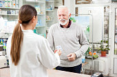 Medicine, pharmaceutics, health care and people concept - Happy senior male customer buying medications at drugstore