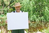 Senior man by pond with blank sign
