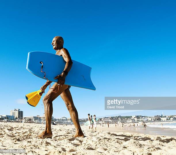 Senior man carrying bodyboard on beach, side view