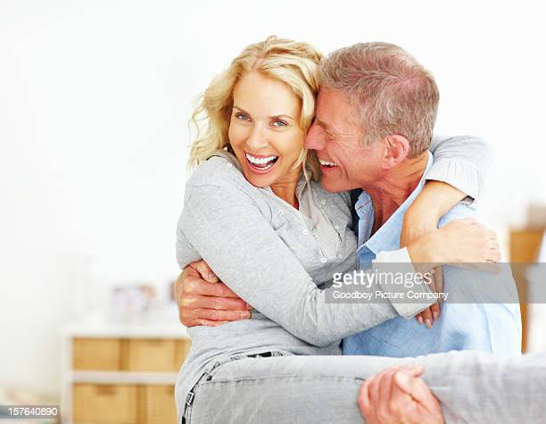 Senior man carrying mature woman in arms
