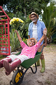 Senior man carrying woman in wheelbarrow while gardening at yard