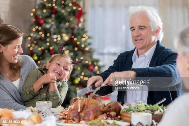 Senior man kerft Turkije tijdens het kerstdiner met familie