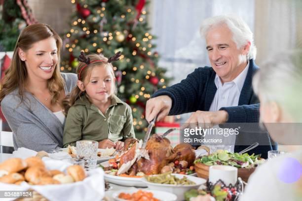 Senior man kerft Turkije voor familie tijdens het kerstdiner