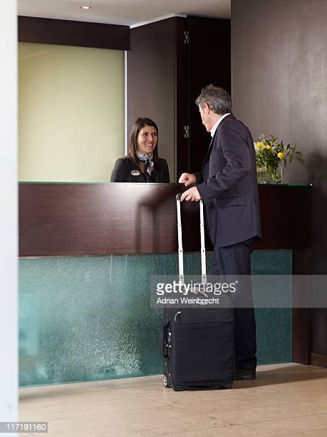 Senior man checking in at front desk of a hotel