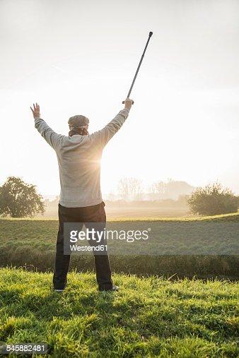 Senior man cheering in rural landscape