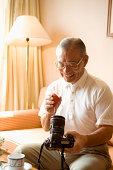 Senior man cleaning camera, smiling