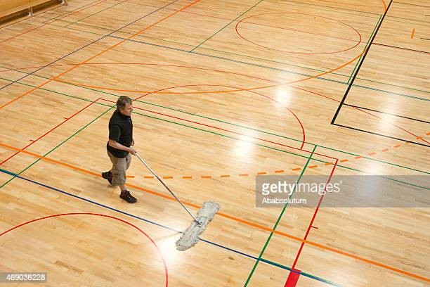 Senior Man Cleaning Floor in School Gymnasium, Europe