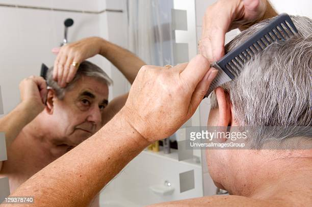 Senior man combing his hair in front of bathroom mirror