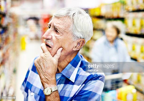 Senior man considers his choice on the supermarket shelf seriously