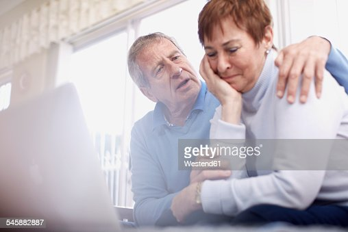 Senior man consoling crying wife at laptop