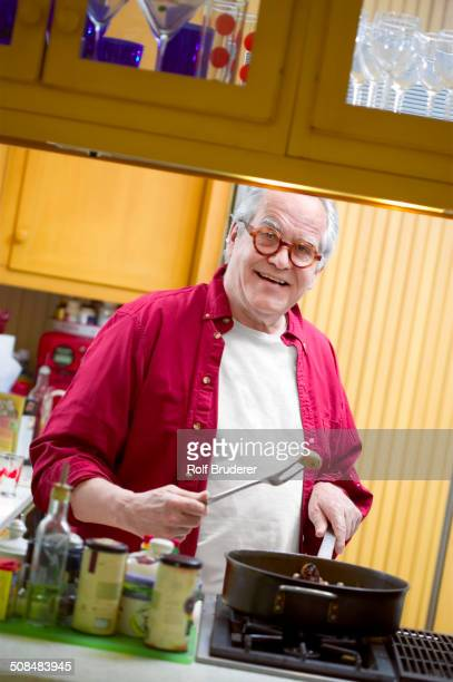 Senior man cooking in kitchen