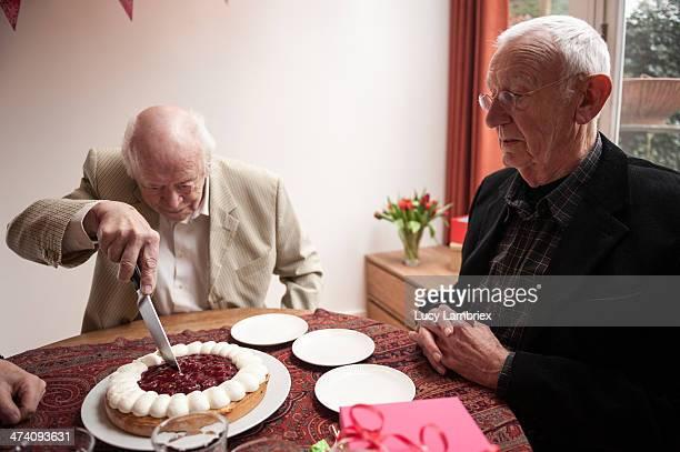 Senior man cutting his birthday cake