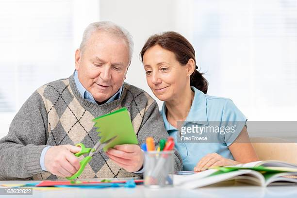 Senior man cutting paper with scissors