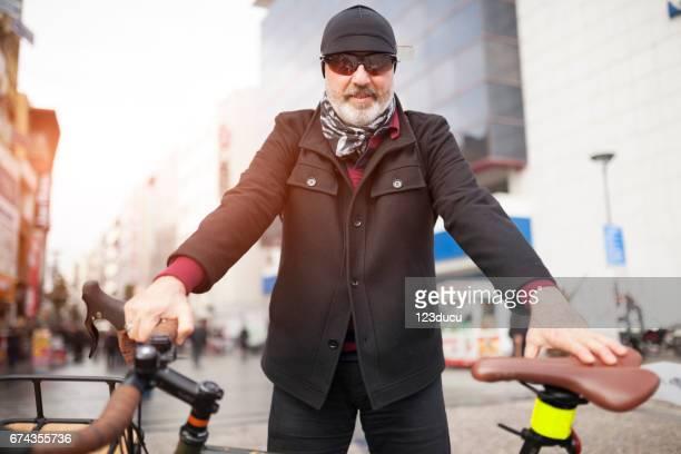 Senior Man Cycling At City Street