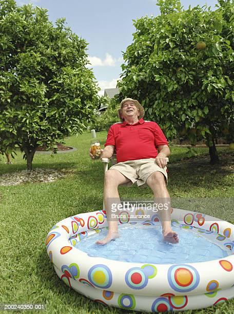 Senior man dangling feet in kiddie pool, holding drink