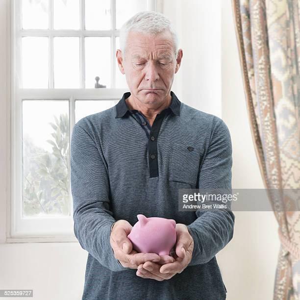 Senior man depressed by size of piggy bank savings