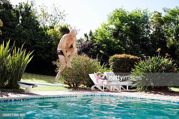 Senior man diving into pool, senior woman sitting on sun lounger