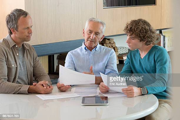 Senior man doing paperwork with son and grandson in a living room