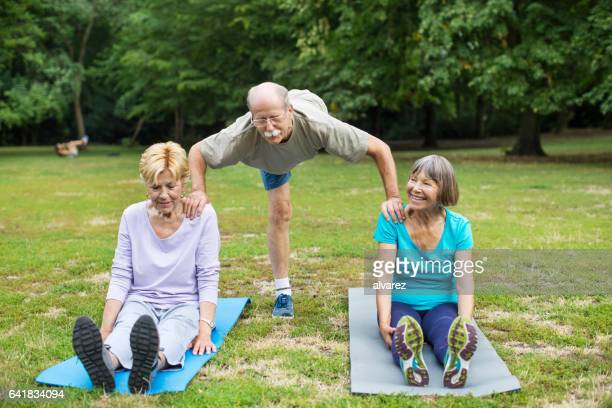 Senior man doing stretching workout with women at park