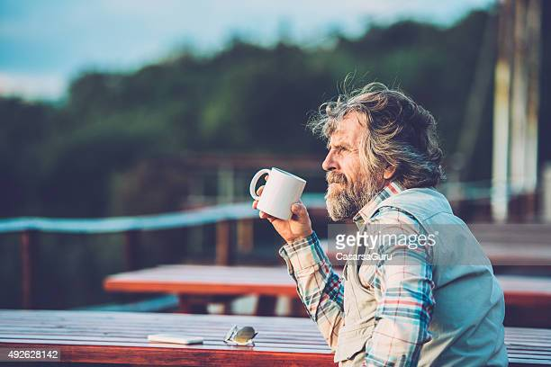 Senior Man Drinking a Coffee or a Tea Outdoors