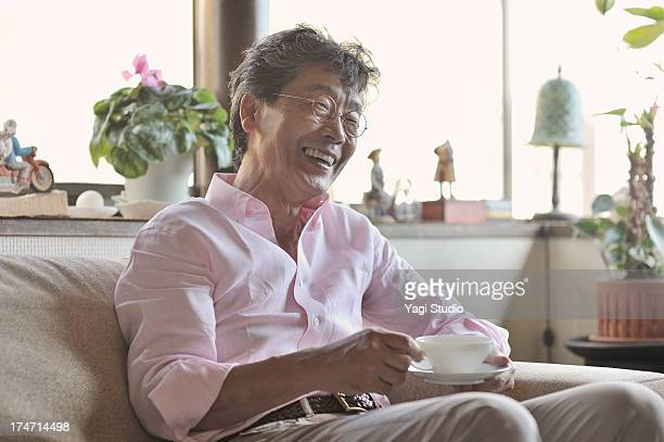 Senior man drinking coffee while sitting on a couc