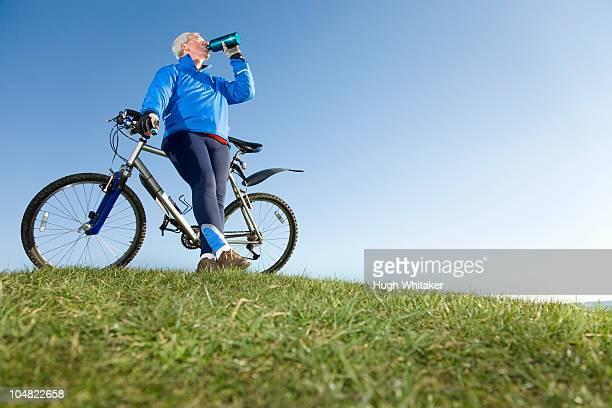 Senior man drinking water on bike ride