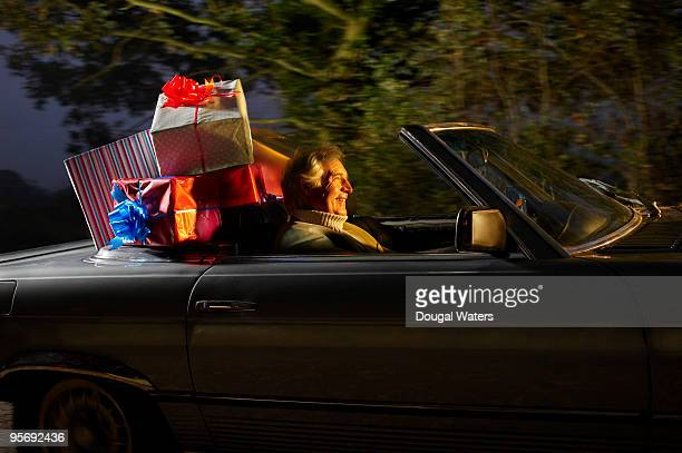 Senior man driving car full of presents.