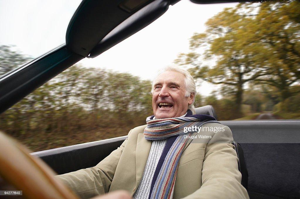 Senior man driving classic car.