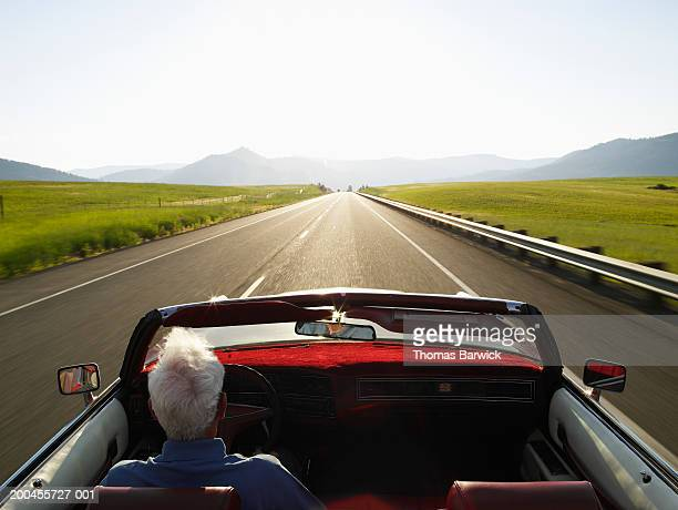 Senior man driving convertible car at sunrise, rear view
