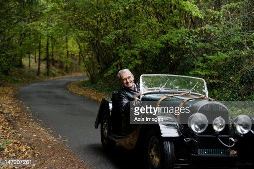 senior man driving in antique car