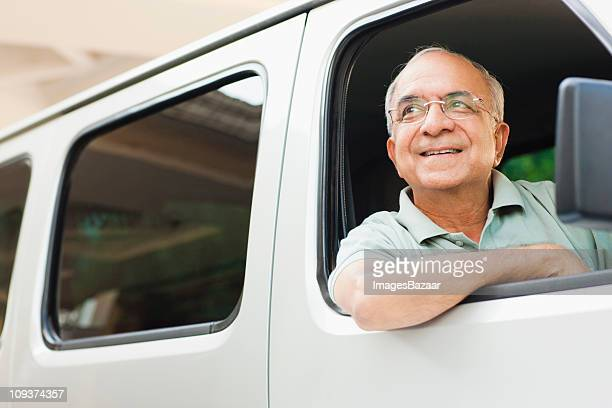 Senior man driving van, looking away