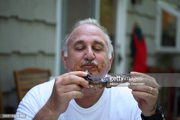 Senior man eating steak, outdoors