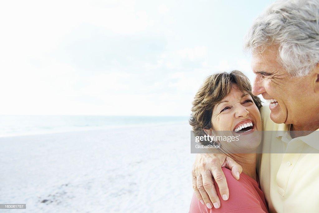 Senior man embracing a smiling woman on beach : Stock Photo