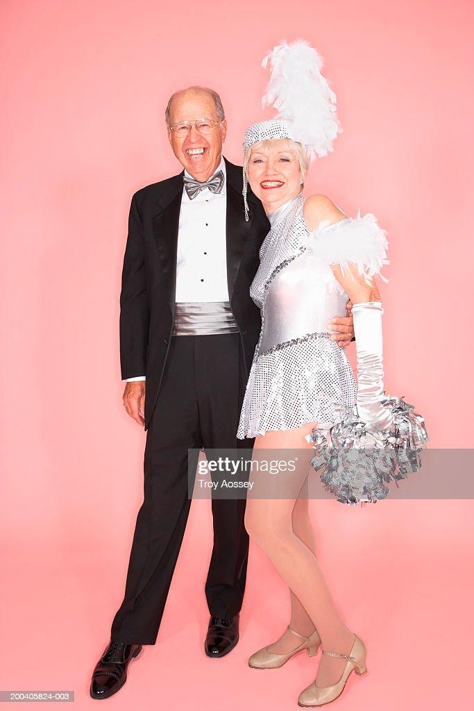 Senior man embracing woman in cheerleader costume, smiling, portrait : Stock Photo