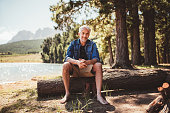Portrait of relaxed mature man sitting on a wooden log near the lake. Mature man enjoying a day at the lake.
