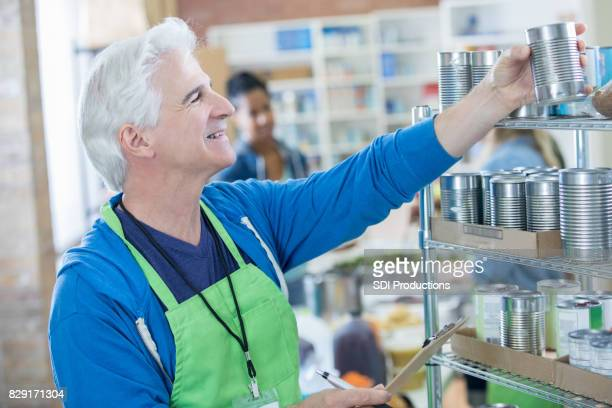 Ältere Mann genießt Freiwilligenarbeit in Lebensmittelbank