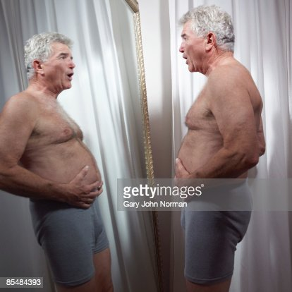 Senior man examines stomach in mirror : Stock Photo