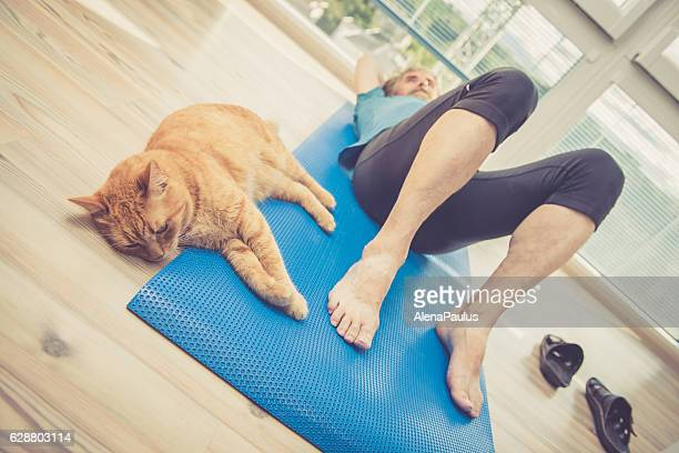 Senior Man exercising at Home with his Ginger Cat