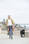 Senior man exercising dog on bicycle
