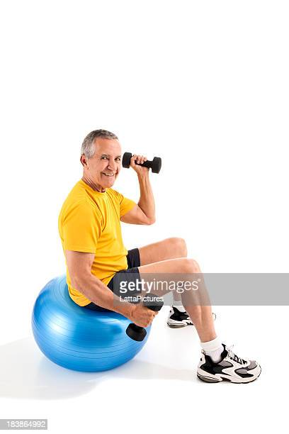 Senior man exercising with dumbells on exercise ball