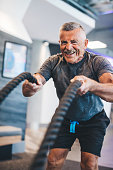 Senior man exercising with ropes at the gym. Physical activity and healthy lifestyle.
