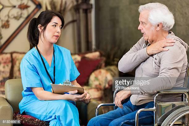 Senior man explains symptoms to nurse