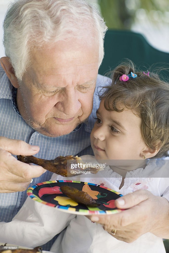 Senior man feeding chicken to his granddaughter : Foto de stock